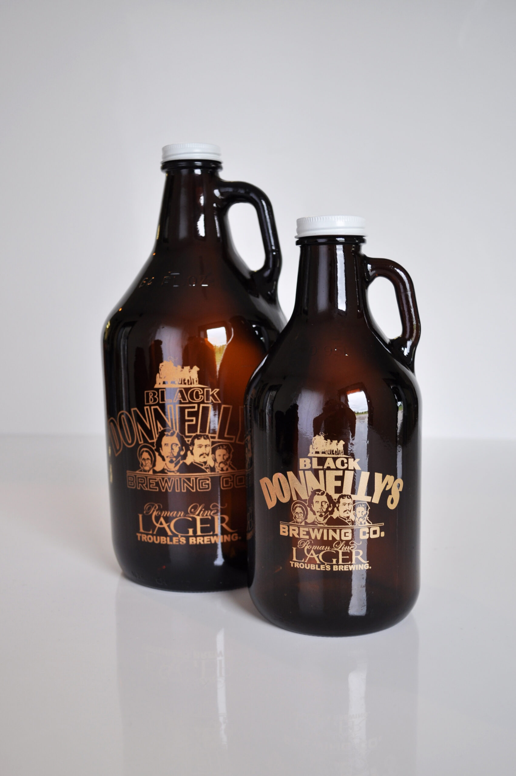 One small and one large Black Donnellys Brewing Company glass beer growlers with handle.
